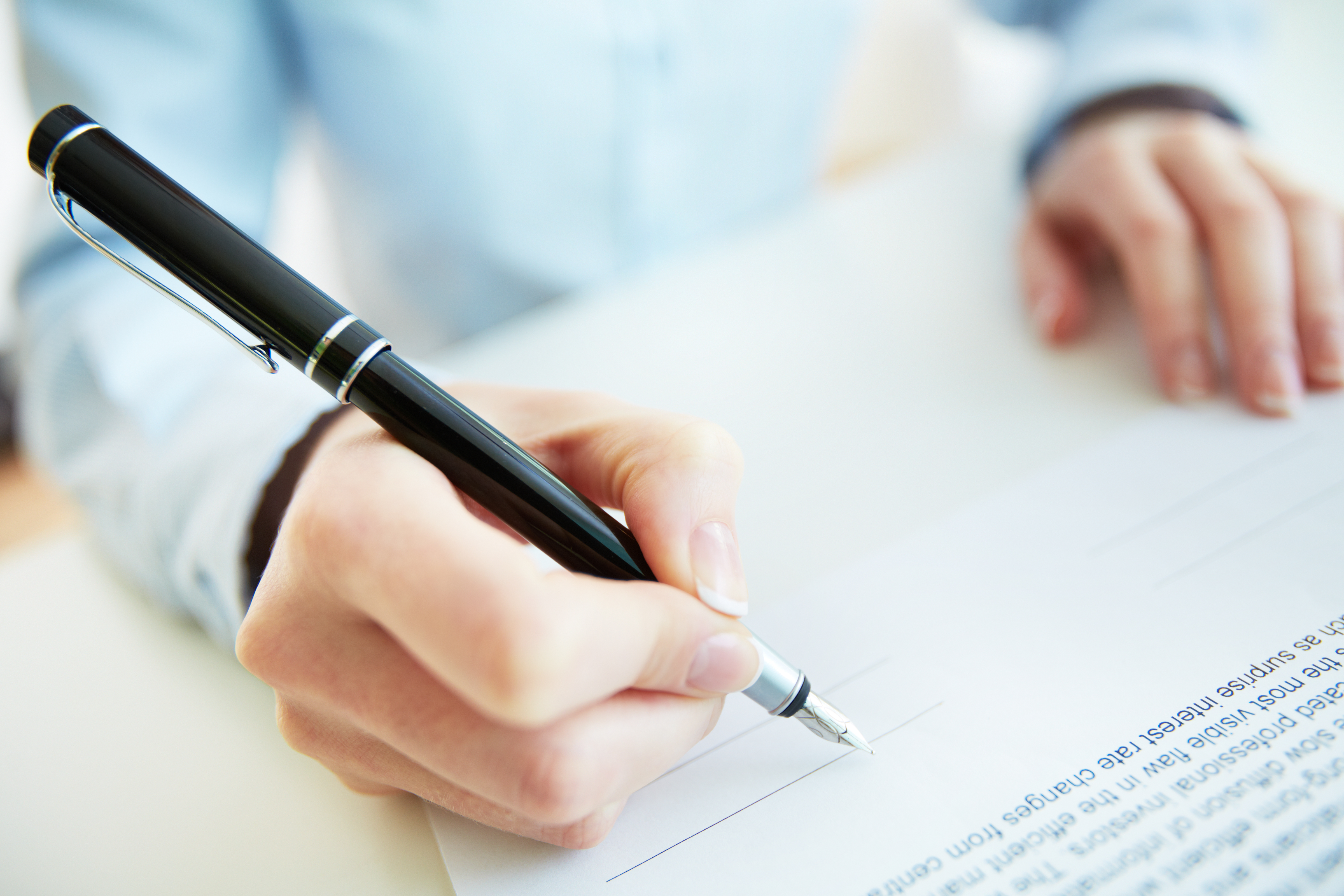 Close-up image of GPs putting their signature to a contract